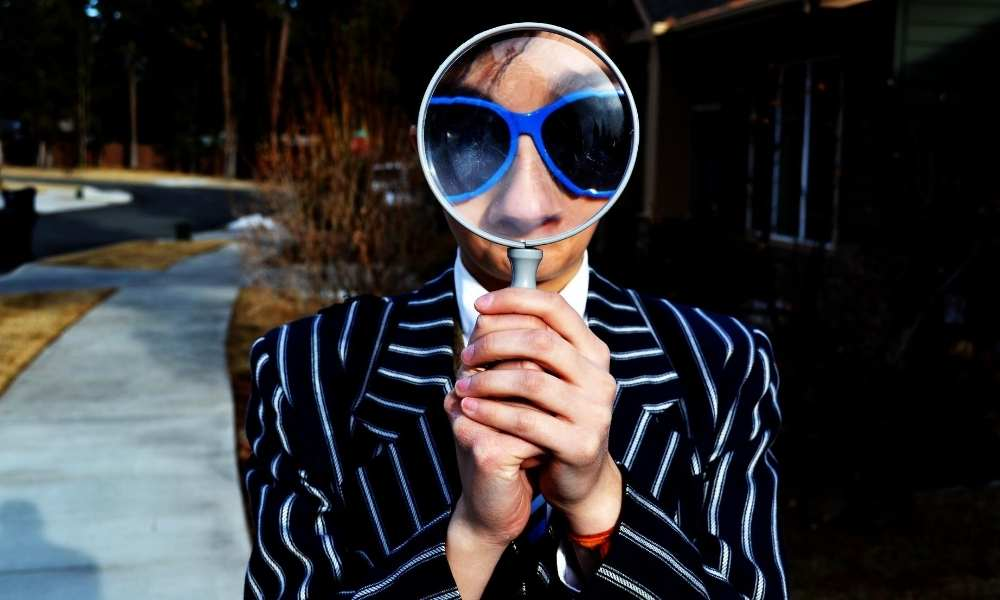 man-looking-through-magnifying-glass-finding-work-recession