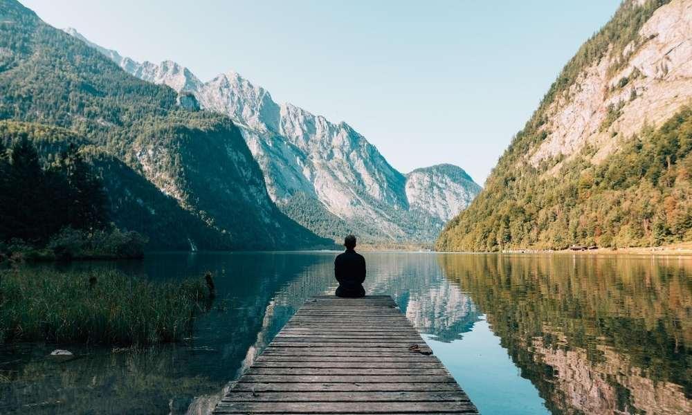 man-meditating-on-pier-by-lake